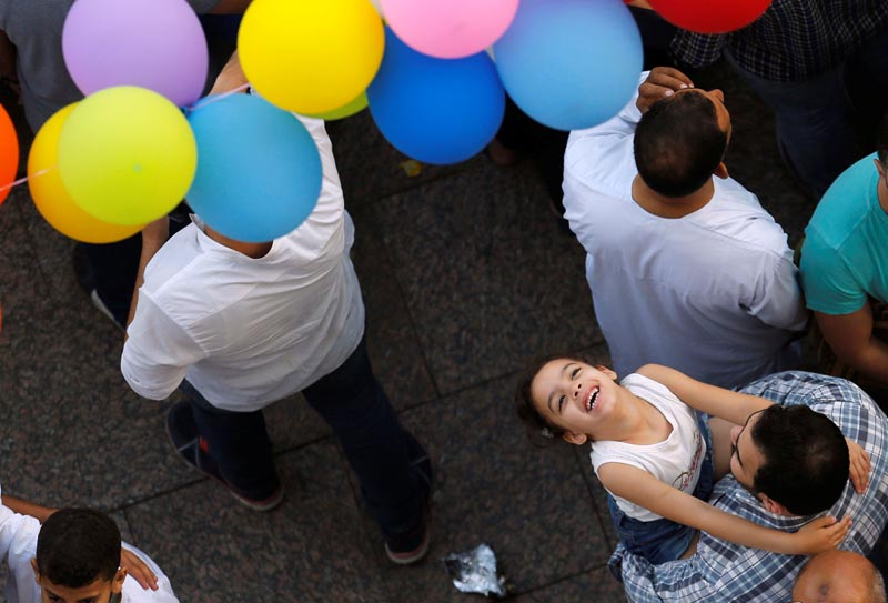 An Egyptian girl smiles and waits to catch balloons, distributed after Eid al-Fitr prayers, marking the end of the Muslim holy fasting month of Ramadan at a public park, outside El-Seddik Mosque in Cairo, Egypt, on June 25, 2017. Photo: Reuters