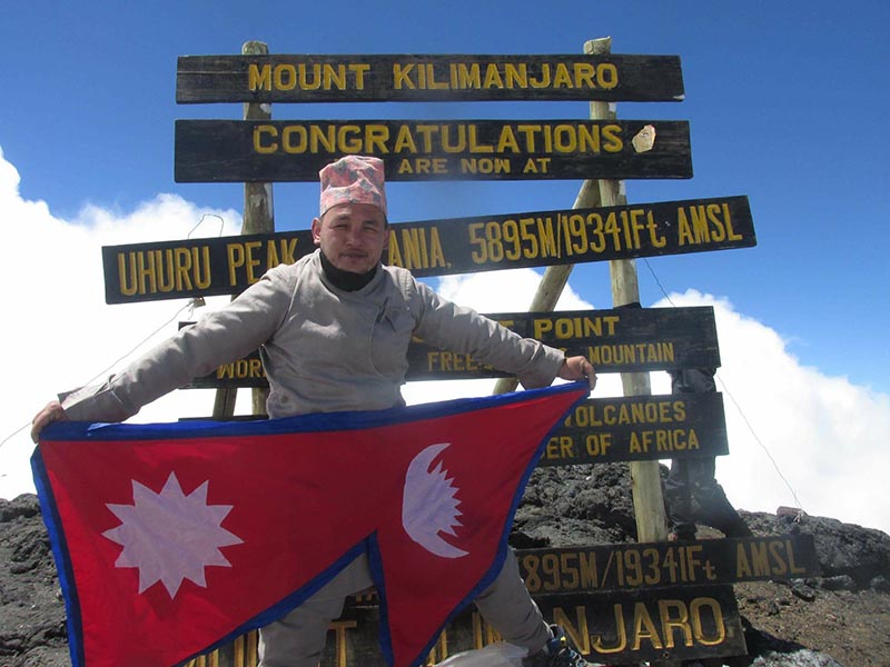 File - Sanjay Pandit, a Nepali climber poses for photo showing a Nepali flag at the summit of Mount Kilimanjaro in Tanzania, Africa. The ultra runner from Nepal's mid-western Pyuthan district, died while descending the Denali Pass after the team successfully scaled the peak on Mt Denali on Friday, June 16, 2017.