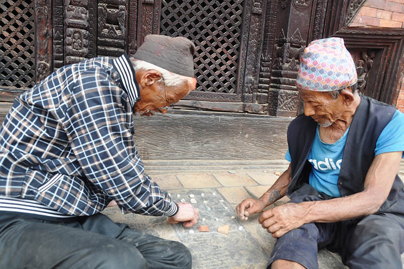 Two elderly kill time by playing Bagchal at the Bhaktapur Durbar Square, on Friday, June 23, 2017. Photo: RSS
