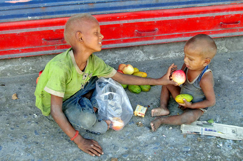 Two minors share fruits after begging around at the Prithvi Chok of Pokhara, on Monday, June 26, 2017. Photo: Rishi Ram Baral