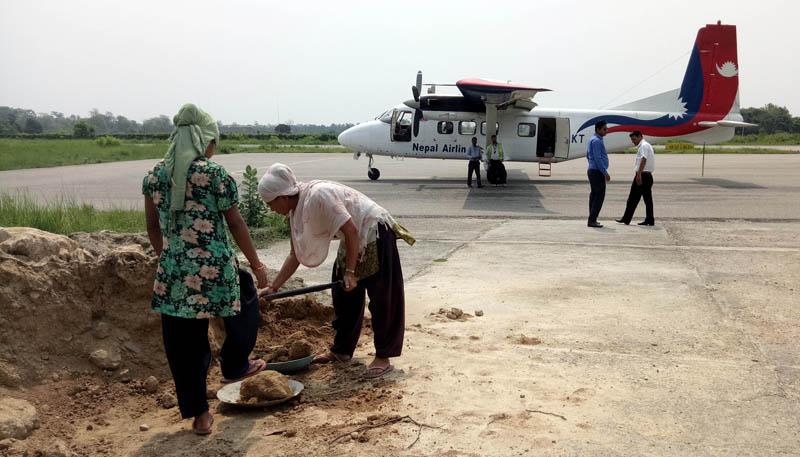 Labourers fill potholes beside the runway at the Simara Airport in Bara district , on Saturday, June 10, 2017. Photo: Ram Sarraf