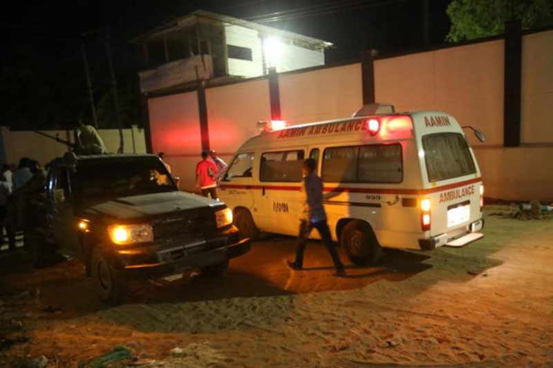 A man walks past an ambulance and armed security forces at the scene of an attack outside an hotel in Mogadishu, Somalia on June 14, 2017. Photo: Reuters