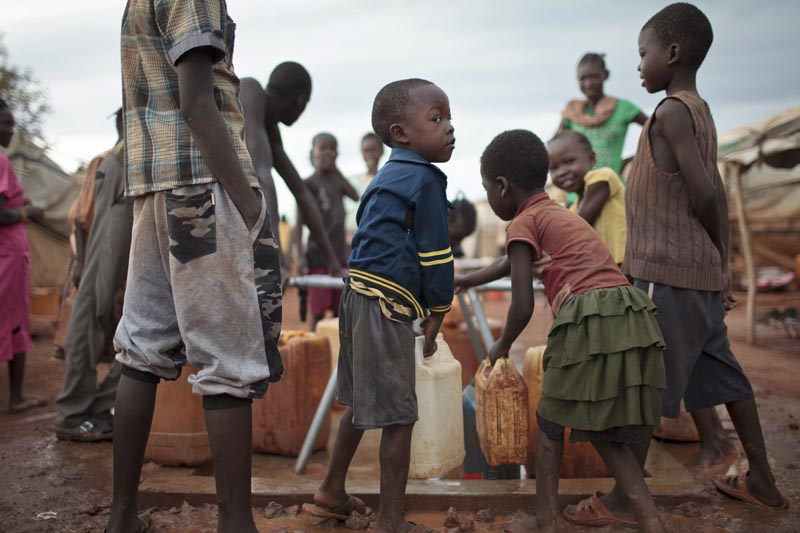 Children queue to carry water from a well in plastic containers at the United Nations' protected camp in Wau, South Sudan, on Sunday, May 14, 2017. Photo: AP