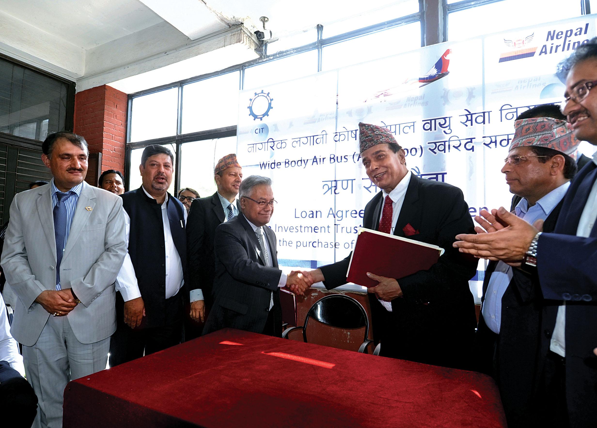 NAC's Managing Director Sugat Ratna Kansakar shaking hands with Executive Director of CIT Ram Krishna Pokharel after signing loan agreement, in Kathmandu, on Monday, June 12, 2017. Photo Courtesy: NAC