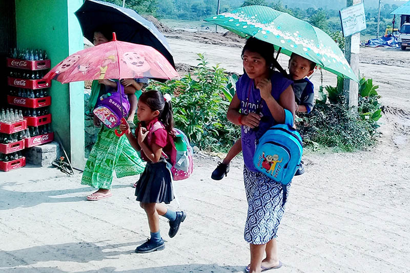 Locals including a minor use an umbrellas to sheild themselves from scorching heat at Bharatpur in Chitwan district, on Tuesday, June 13, 2017. Photo: RSS