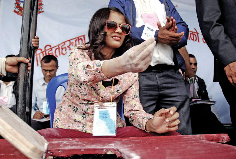 A visually impaired women picking a lottery coupon to decide the owner of a new taxi in a draw held to distribute taxis among earthquake victims of Nuwakot distirct, at Chyasal, in Lalitpur, on Wednesday, June 21, 2017. Photo: Naresh Shrestha/ THT