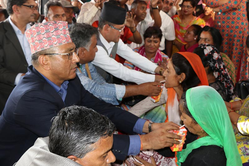 Secretary of Ministry of Education Shanta Bahadur Shrestha offering juice to temporary teachers who ended their fast unto death protest programme on the eighth day, at Bhadrakali in Kathmandu on June 23, 2017. Photo: RSS