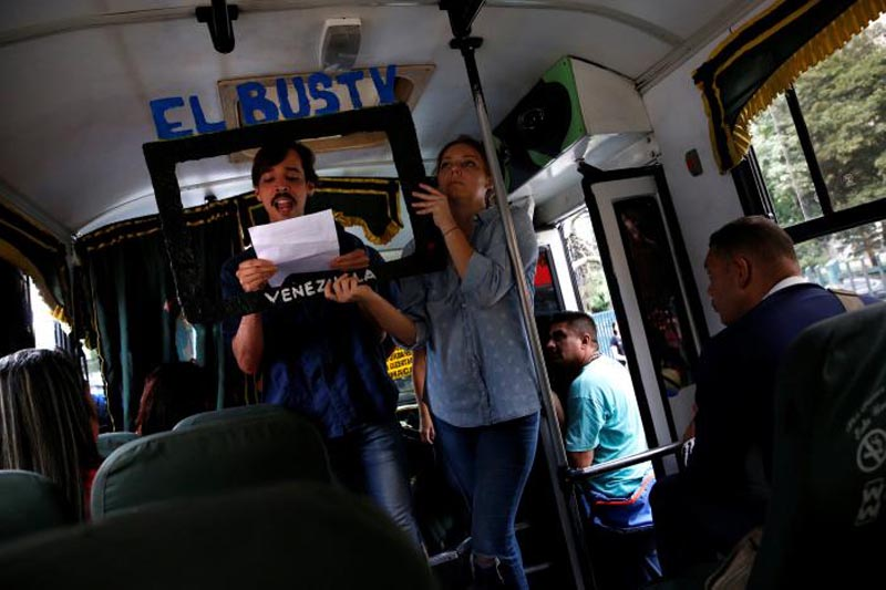 Members of an artistic group perform a 'TV news show' on a public transportation bus in Caracas, Venezuela, June 10, 2017. Picture taken June 10, 2017. The cutout reads 'The Bus TV'. Photo: Reuters