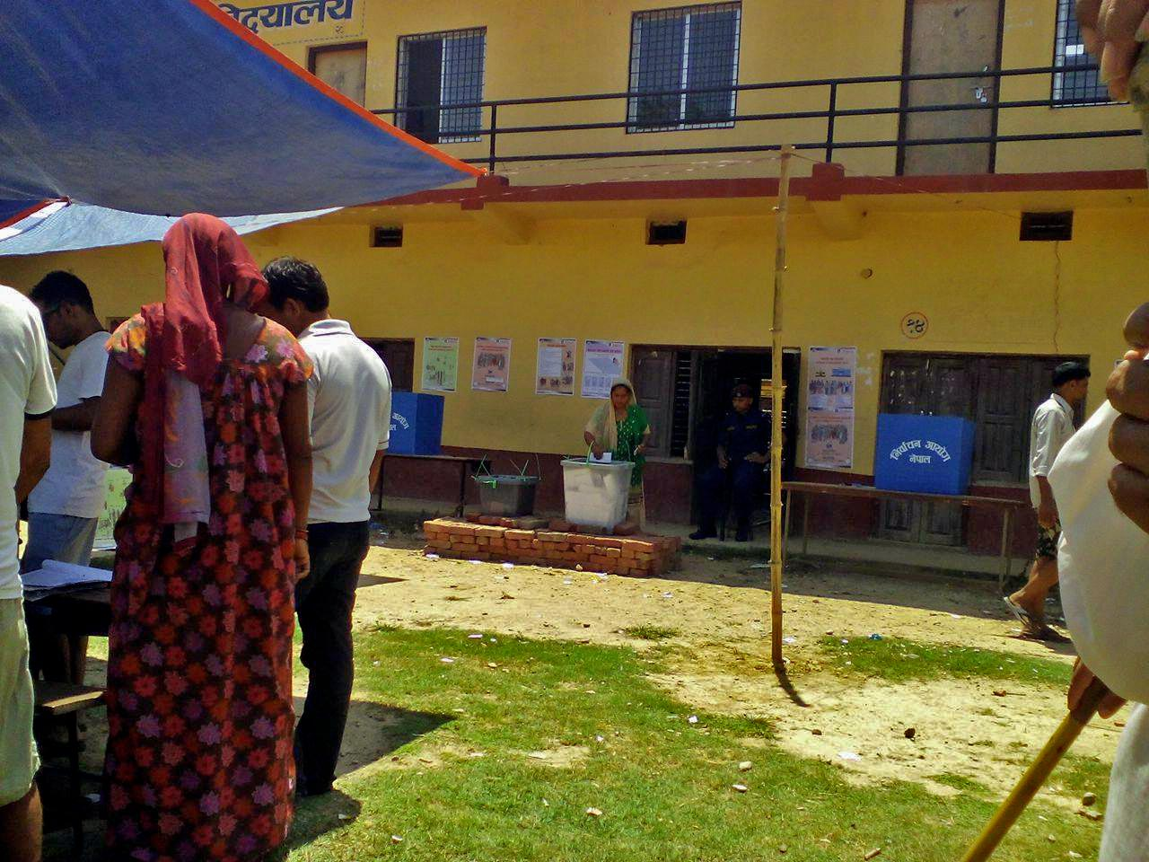 A woman is seen casting her vote as a security personnel watches, in the second phase of elections in the polling centre at GyanJyoti Higher Secondary School, Chapargaudi of Kohalpur Municipality-12 in Banke district, Province 5, on Wednesday, June 28, 2017. Photo courtesy : Santosh Shahi