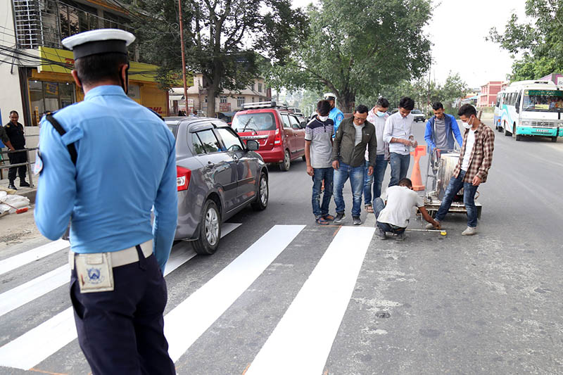 A traffic police looks on as the workers prepare to paint a zebra crossing on a road along the Koteshwor-Gausala road section near Tribhuvan International Airport in Singamangal of KMC-9, on Sunday, June 4, 2017. Photo: RSS