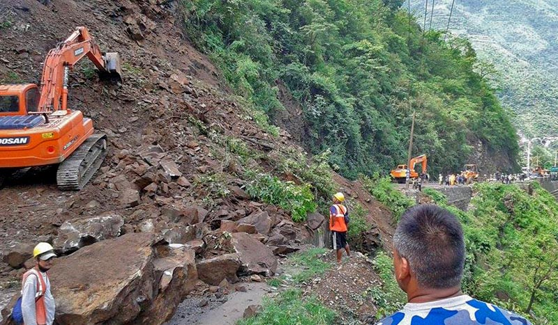 FILE PHOTO: Excavators are seen clearing the landslide debris deposited on the road near Kalikhola along Narayangadh-Muglin road section, on Friday, June 23, 2017. Photo: RSS