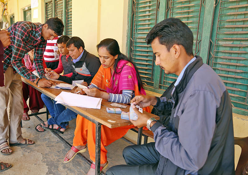 Election Commission officials distributing voter identity card at a local school premises in Dadeldhura district, on Monday, June 26, 2017. Photo: RSS