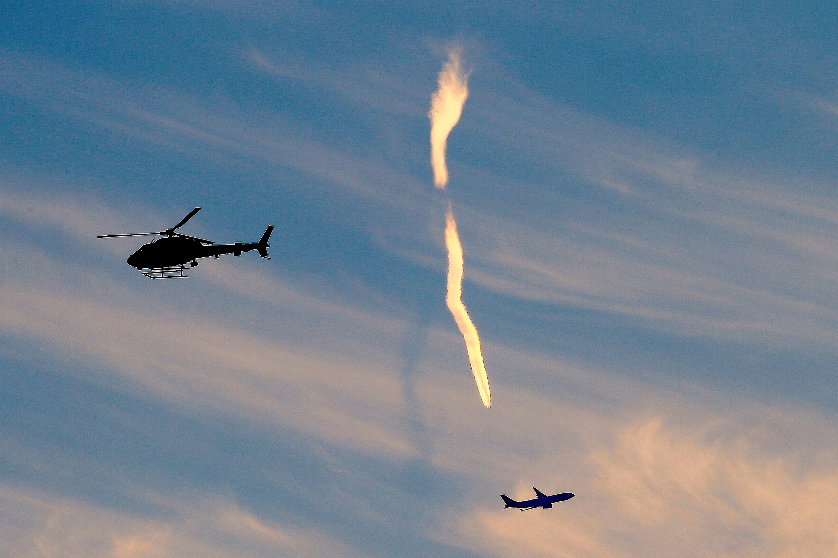 The trail of an aeroplane can be seen amongst clouds and between a helicopter and a plane in the sky above Sydney in Australia. Photo: Reuters/ File