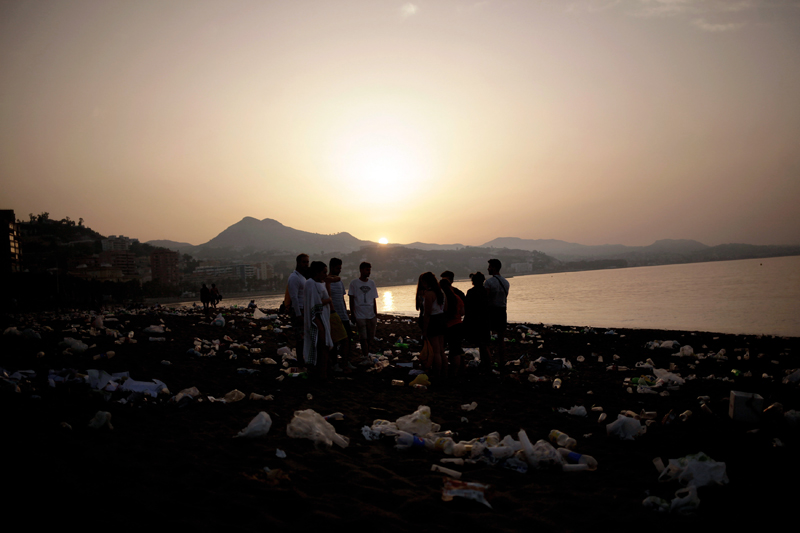 Yound people stand surrounded by rubbish at dawn at Malagueta beach after celebrating the summer solstice in Malaga, Spain June 24, 2017. Photo: Reuters