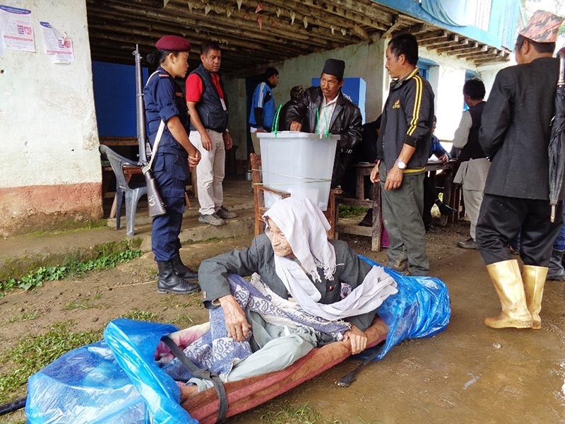 A voter carried on a stretcher to a polling centre in Fakfothum Rural Municipality in Ilam on June 28, 2017. Photo: RSS