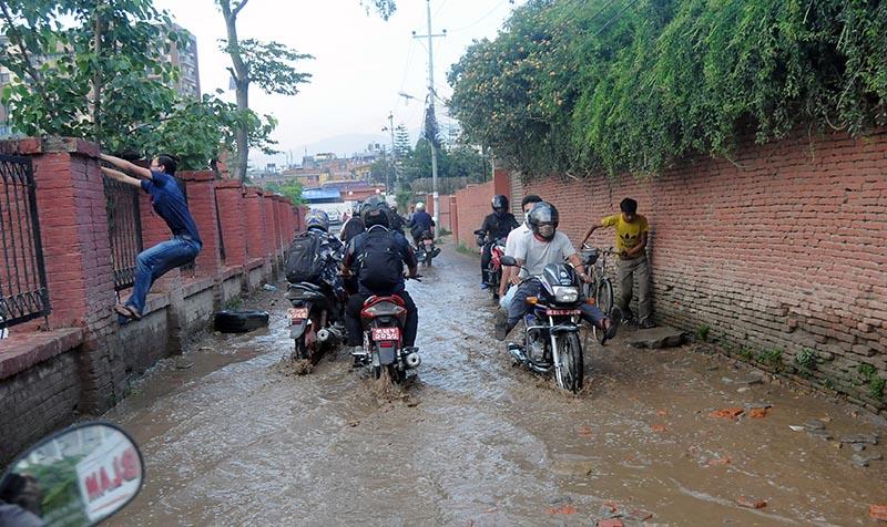 A pedestrian clinging to a fence to pass through a waterlogged street, in Kamalpokhari, on Monday, June 5, 2017. Photo: Balkrishna Thapa Chhetri/THT
