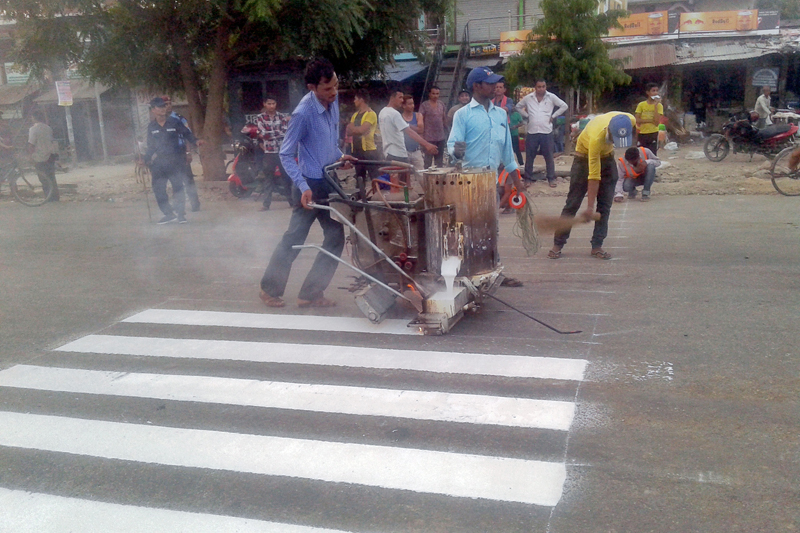 Zebra crossing being painted on a road at Jhalari Bazaar of Kanchanpur district, on Monday, June 12, 2017. Photo: RSS
