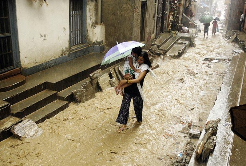 A woman carrying a child walking through a flooded alley, at Bagalamukhi, Lalitpur, on Friday, July 28, 2017. Photo: Naresh Shrestha/THT