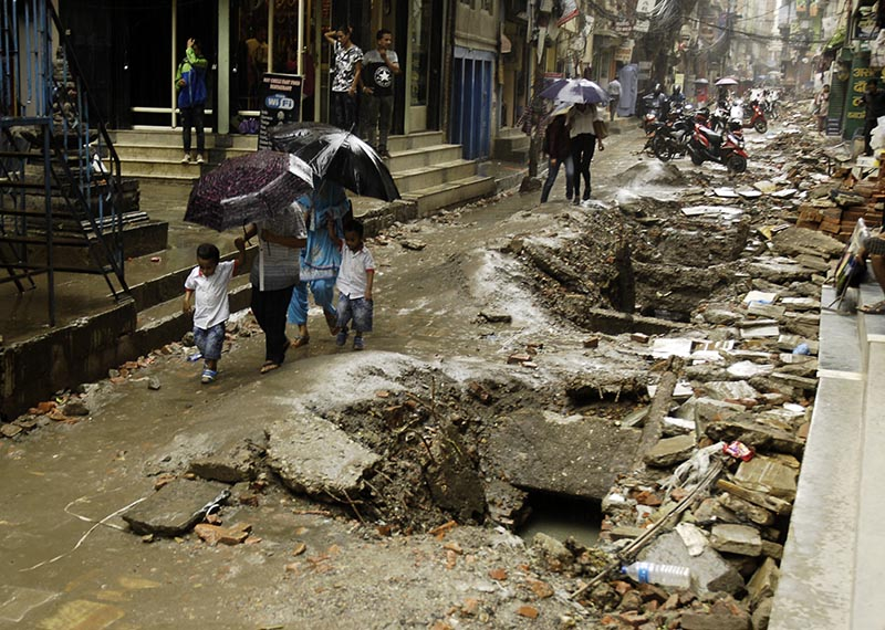 People walking along a badly damaged road as it rains in Bangemuda, Kathmandu, on Wednesday, July 19, 2017. Potholes pose a great risk to motorists and pedestrians during heavy rainfall. Photo: THT