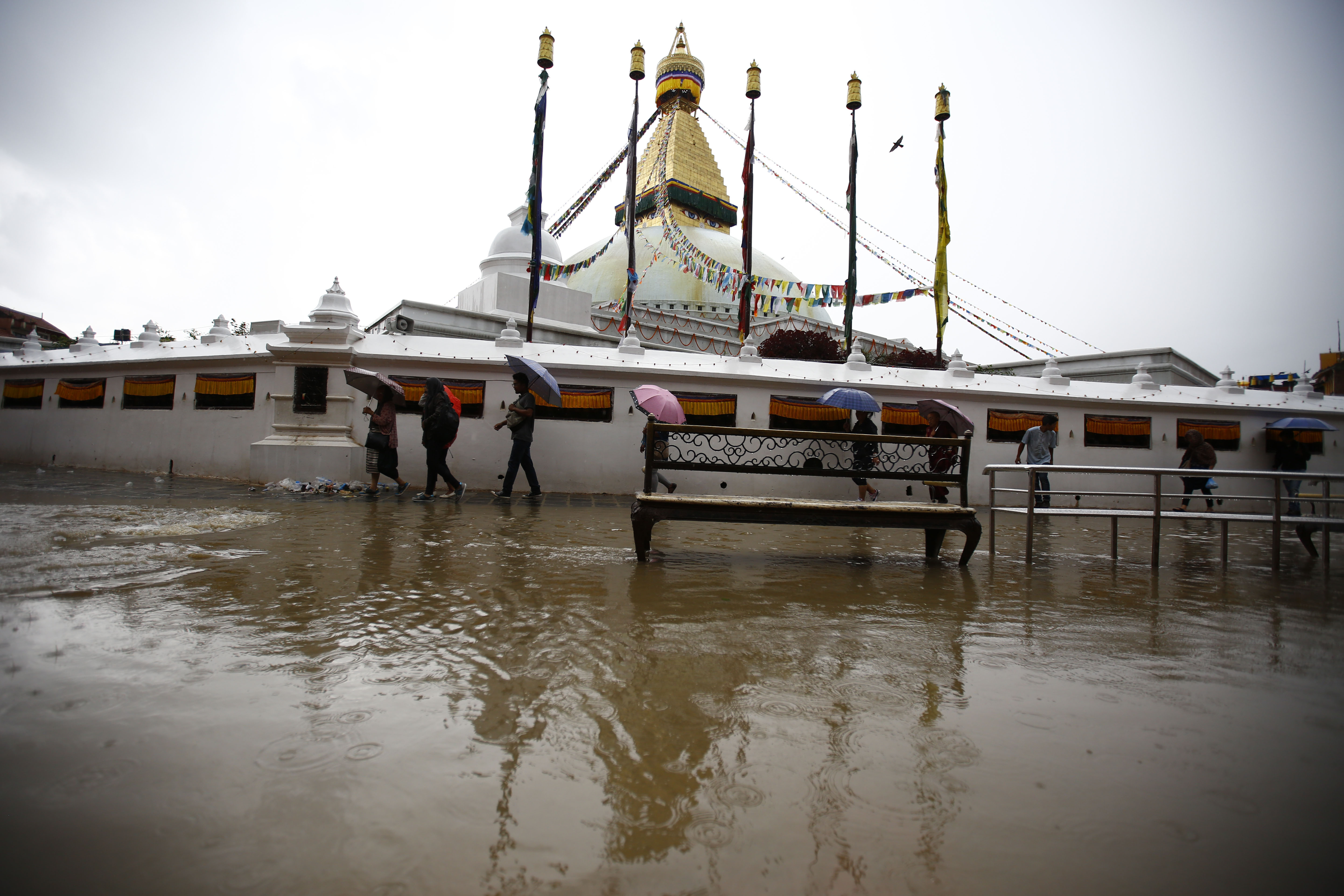 People struggling to walk around the inundated Boudhanath Stupa, a UNESCO World Heritage site, as captured on Sunday, July 23, 2017. During monsoon the area is inundated due to poor drainage system in the tourist hub. Photo: Skanda Gautam