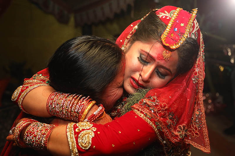A bride embraces her relative during a wedding ceremony in Kathmandu, publiced on Sunday, July 23, 2017. Courtesy: Chyangba Lama