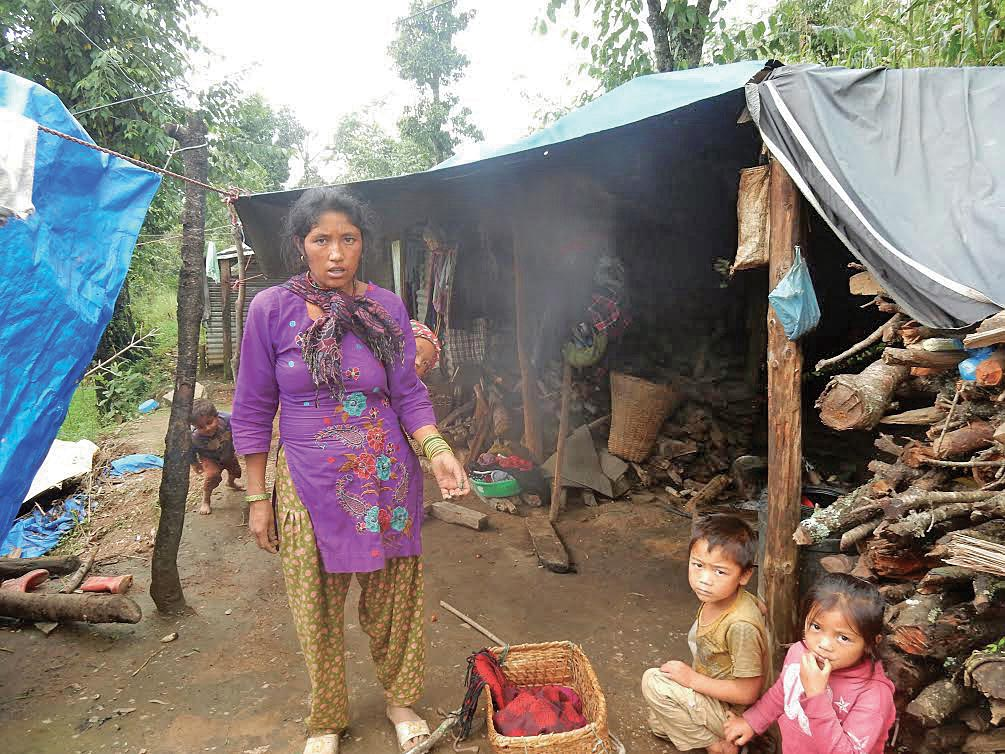 A woman standing outside a hut with her children, in Dolakha, on Saturday. Photo: THT