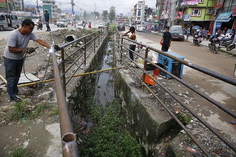 Workers welding guardrails along an open drainage channel, in Samakhusi, Kathmandu, on Sunday, July 30, 2017. Photo: Skanda Gautam/THT