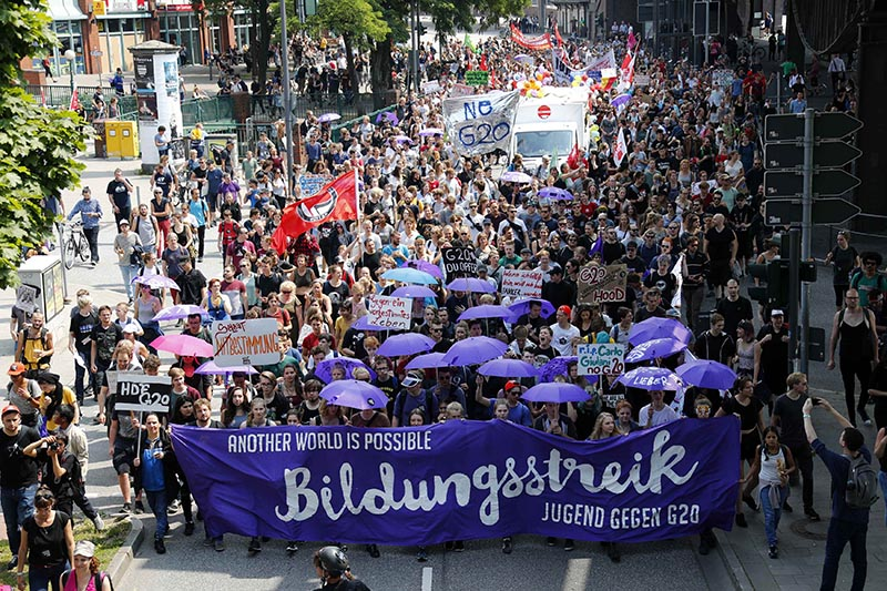 People hold banners and umbrellas as they walk during the protest demonstration at the G20 summit in Hamburg, Germany, on July 7, 2017. Photo: Reuters
