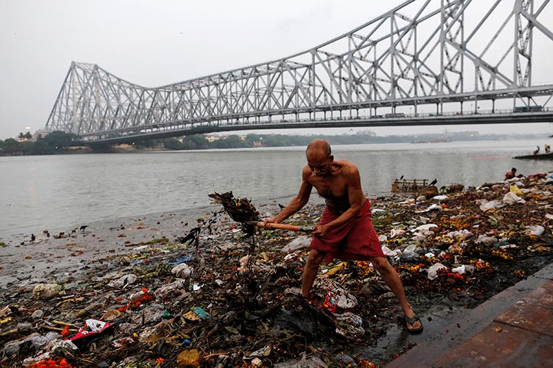 A man cleans garbage along the banks of the river Ganges in Kolkata, India, on April 9, 2017. Photo: Danish Siddiqui/ Reuters