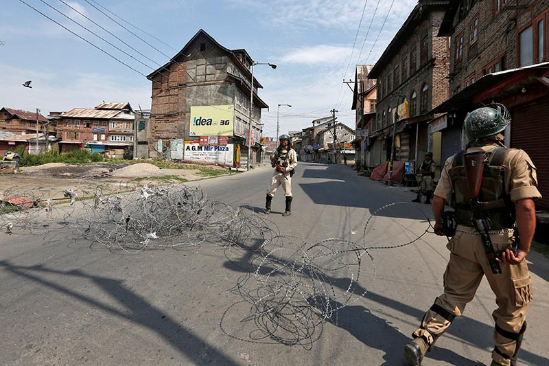 An Indian policeman pulls concertina wire to lay a barricade on a deserted road during restrictions a day before the death anniversary of Burhan Wani, a commander of the Hizbul Mujahideen militant group, in downtown Srinagar, on July 7, 2017. Photo: Reuters