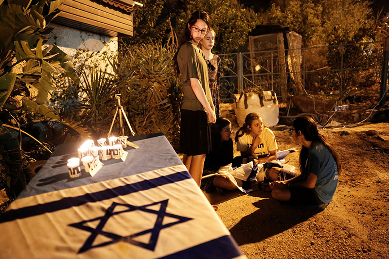 Youths gather next to candles and an Israeli flag placed next to the home where three Israelis were killed in a stabbing attack yesterday in the Jewish settlement of Neve Tsuf, in the occupied West Bank, on July 22, 2017. Photo: Reuters