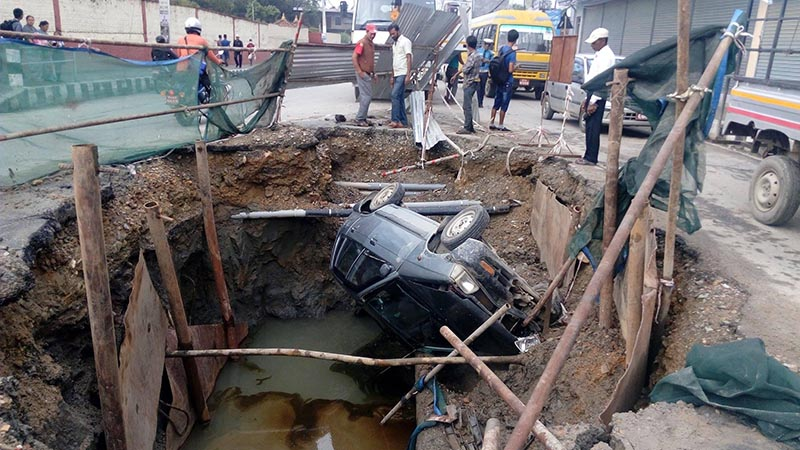 A car lying in a pit dug by Melamchi Water Supply Project in Maharajgunj, on Thursday, July 20, 2017. Photo courtesy: Dipendra Bhandari