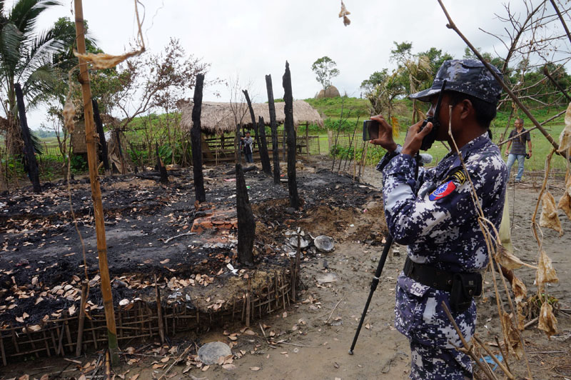 A Myanmar border guard police officer takes pictures at the remains of a burned house in Tin May village, northern Rakhine state, Myanmar, on July 13, 2017. Photo: Reuters