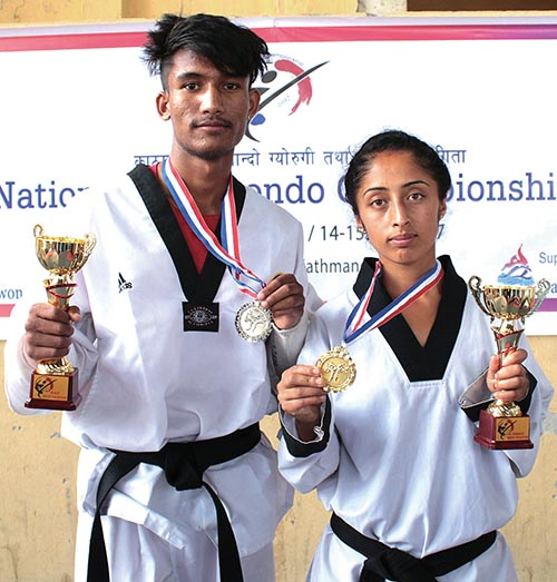 Best fighters of the fifth National Taekwondo Tournament, Bibek BK and Binita Ghimire with trophies in Kathmandu on Saturday. Photo: THT