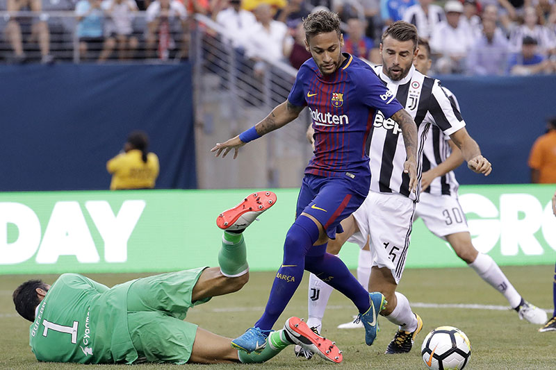 Barcelona's Neymar, center, attacks as Juventus goalkeeper Gianluigi Buffon, left, tries to block his shot during the first half of an International Champions Cup soccer match, Saturday, July 22, 2017. Photo: AP