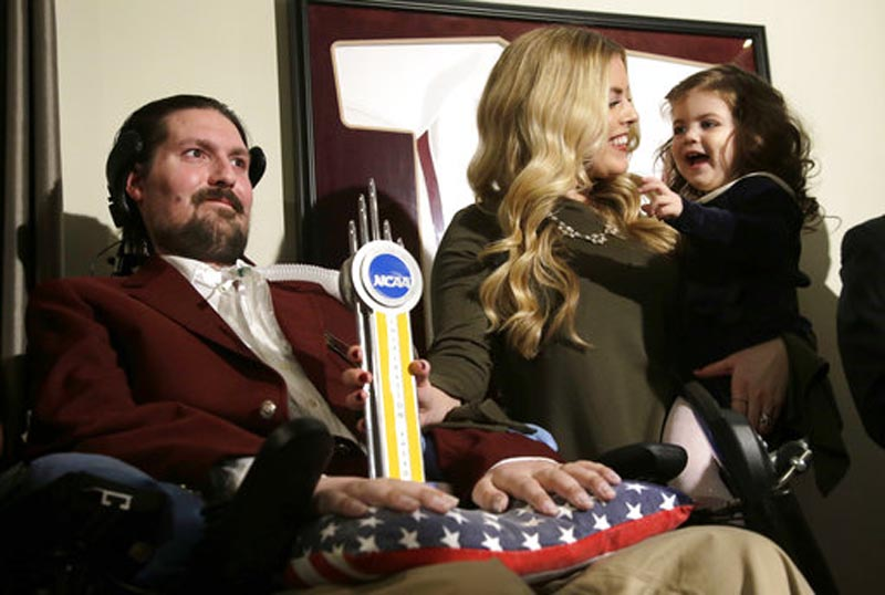 FILE - In this December 13, 2016, file photo, former Boston College baseball captain Pete Frates, left, appears with his wife Julie, center, and two-year-old daughter Lucy, right, moments after he was presented with the 2017 NCAA Inspiration Award, at their home in Beverly. Photo: AP