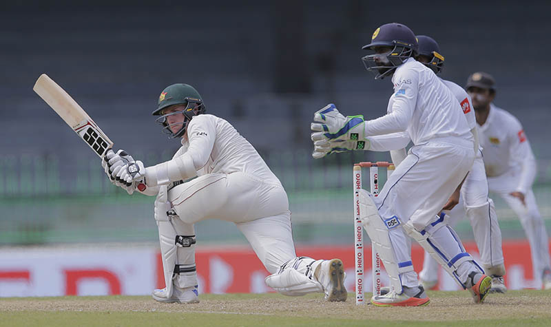 Zimbabwe's Peter Moor plays a shot in front of Sri Lanka's Niroshan Dickwella watches during the first day's play of the only test match between Sri Lanka and Zimbabwe in Colombo, Sri Lanka, Friday, July 14, 2017. Photo: AP