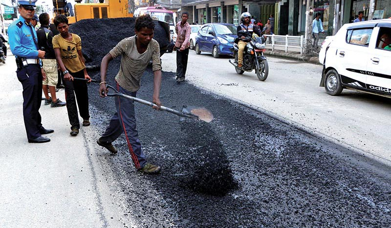 Workers of the Department of Roads blacktopping the busy road in Jamal, Kathmandu, on Monday, July 24, 2017. Photo: RSS