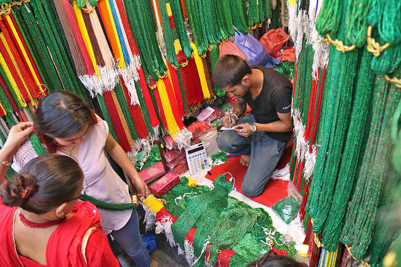 A woman tries a green pote, as Shrawan fervour has gripped Kathmanduities, at a shop in Kathmandu, on Sunday, July 16, 2017. Photo: RSS