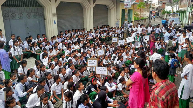 Students and teachers running class on the road in front of the Sundarmal Ramkumar Girls Higher Secondary School in Birta, of Birgunj of Parsa district, protesting against the principal's decision to start summer vacation earlier than scheduled, on Sunday, July 02, 2017. Photo: Ram Sarraf