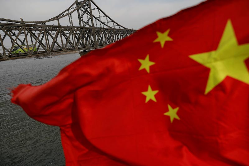 A Chinese flag is seen in front of the Friendship bridge over the Yalu River connecting the North Korean town of Sinuiju and Dandong in China's Liaoning Province, on April 1, 2017. Photo: Reuters/ File