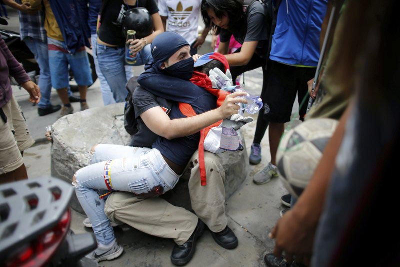 An anti-government demonstrator holds a fellow protester who was injured during clashes with Venezuelan Bolivarian National Guard on the first day of a 48-hour general strike in protest of government plans to rewrite the constitution, in the Bello Campo neighborhood of Caracas, Venezuela, on Wednesday, July 26, 2017.