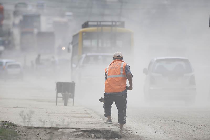 Cloud of dust engulfs a worker in Kathmandu. Photo: Skanda Gautam