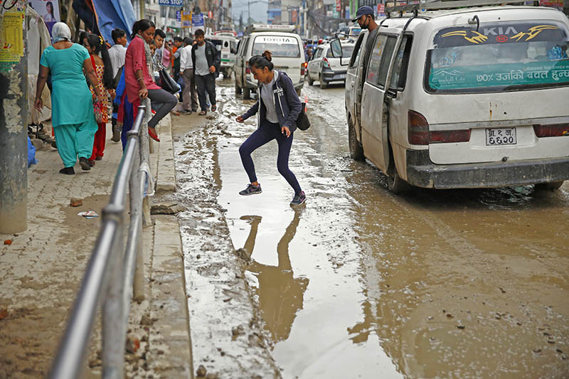 A girl attempts to get across a muddy waterlogged road along the Chabahil-Boudha stretch. Photo: Skanda Gautam