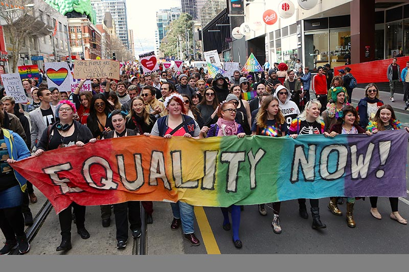 People carry banners and signs as they participate in a marriage equality march in Melbourne, Australia, August 26, 2017. Photo: AAP/David Crosling via Reuters