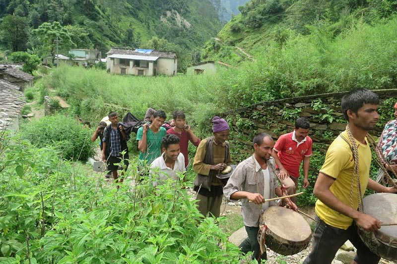 A newborn boy being taken home from Jugada Health Post accompanied by the playing of traditional musical instruments to celebrate his birth in Badimalika Municipality, Bajura, on Monday, August 28, 2017. Photo: THT