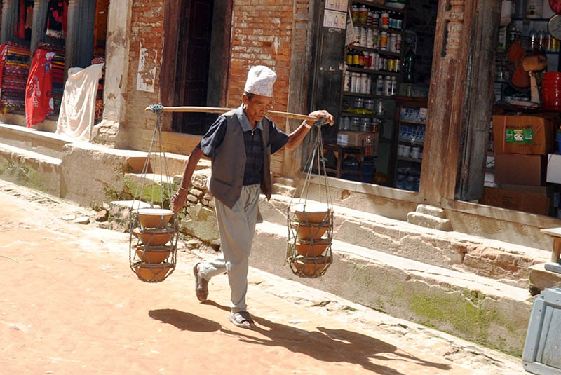 A vendor heading to a market to sell his homemade curd in Bhaktapur district, on Friday, August 11, 2017. Photo: RSS