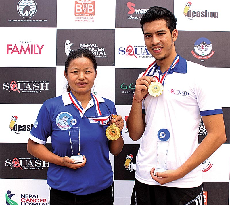 Bhawana Sunuwar and Arahant Keshar Singh hold the trophies and medals after the Dhana Laxmi Maharjan nMemorial Squash Tournament in Lalitpur, on Saturday. Photo: THT