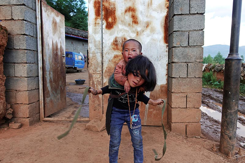 A girl ties a baby onto her back outside a farmhouse on the outskirts of Butuo County, Sichuan province, China, on July 20, 2017.Photo: Reuters