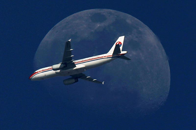 A China Eastern Airlines passenger jet passes in front of the moon over Shanghai, on May 13, 2011. Photo: Reuters/ File